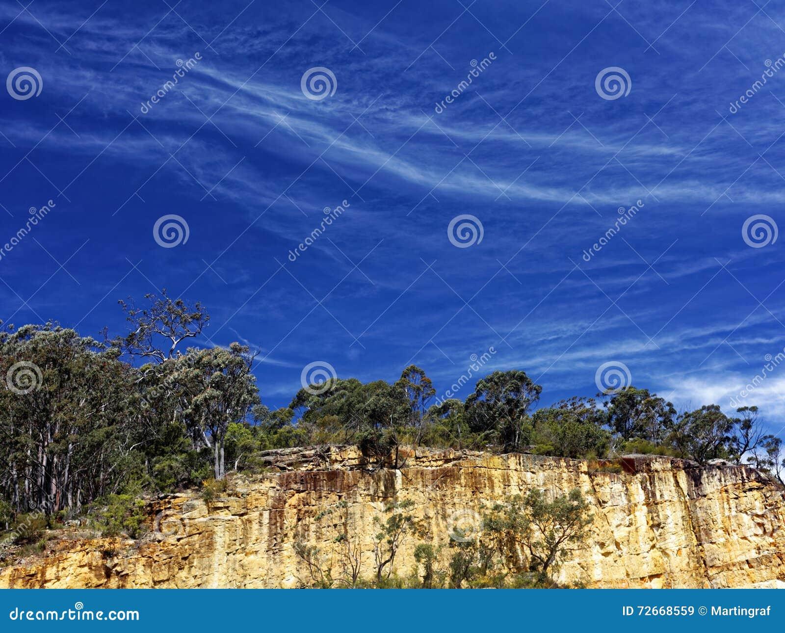 klippenlandschaft durch reichen blauen himmel mit federwolkewolken
