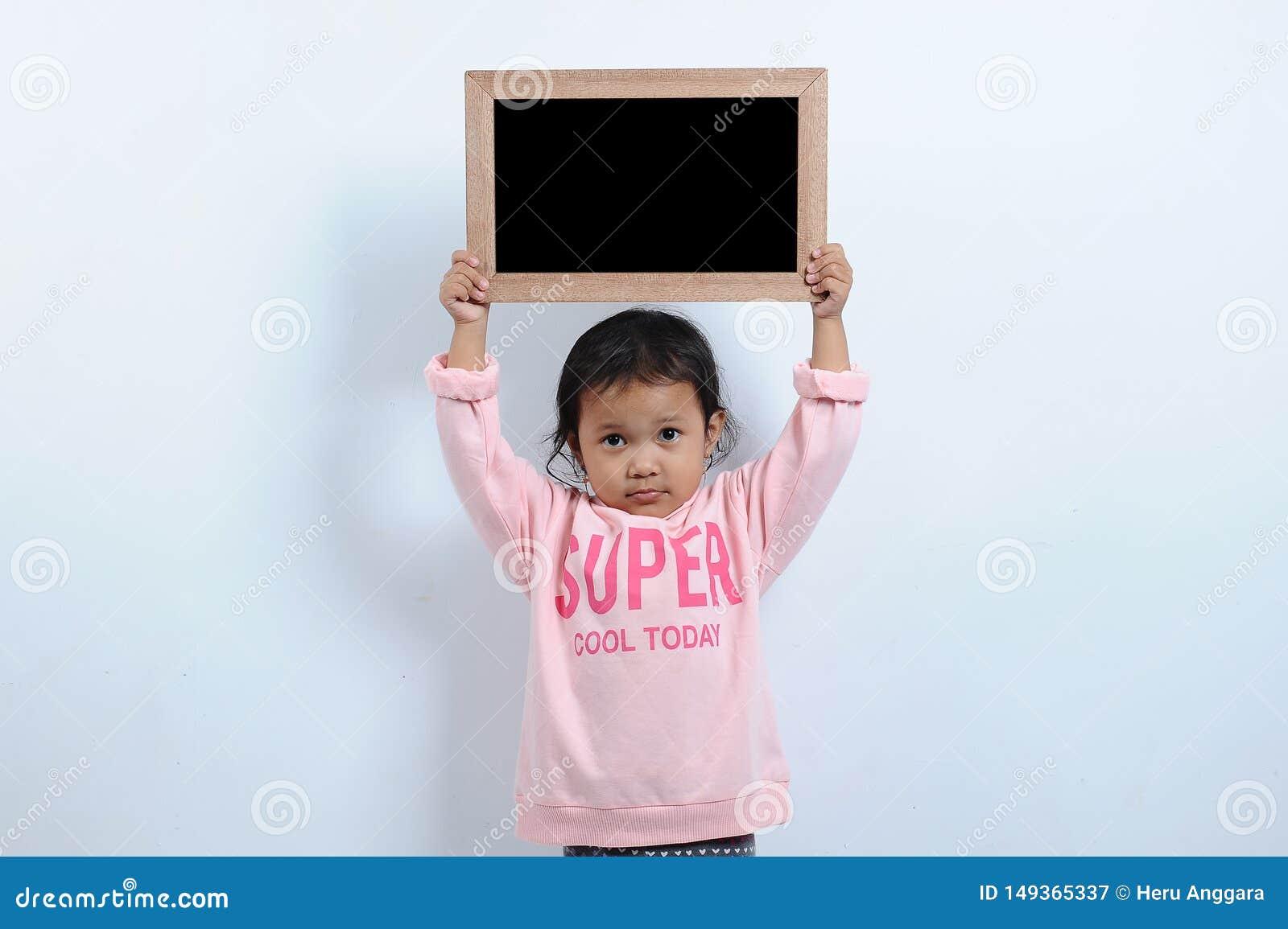 Klippt asiatisk flicka som rymmer den tomma svart tavlan eller svart tavla Du kan smsa det tillbaka till skola