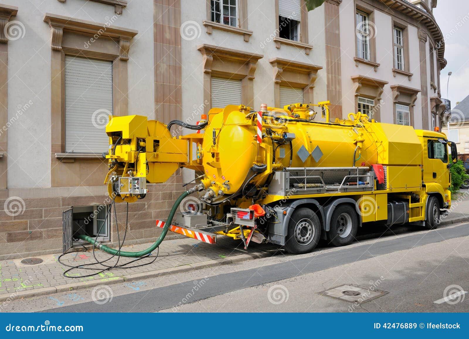 Kloaklastbil som arbetar i stads- stadsmiljö