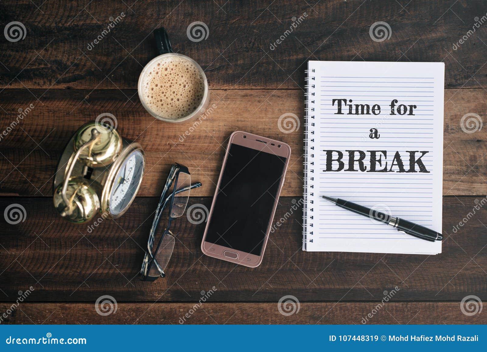 Klockan exponeringsglas, telefonen, kaffe, rånar och anteckningsboken med TIME FÖR ett AVBROTTSord