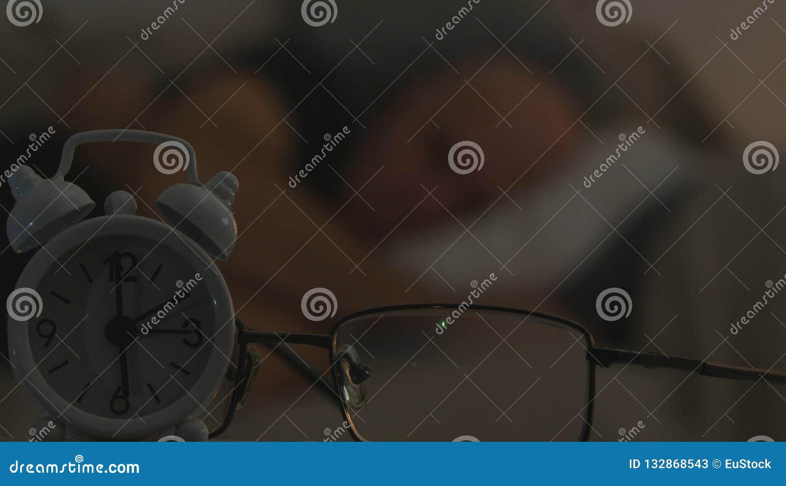 Klok en Oogglazenbeeld met een Mensenslaap op Bank op een Vage Achtergrond
