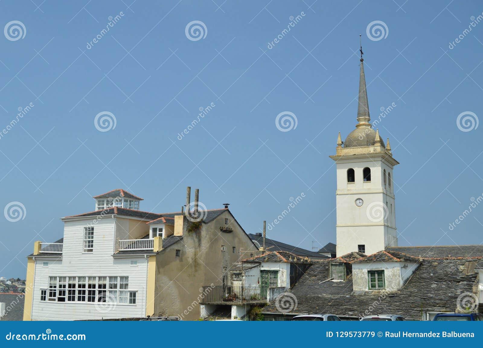 Klokketoren van Santiago Apostol Church And Houses met zeer Oude die Daken praktisch in Castropol worden gebroken