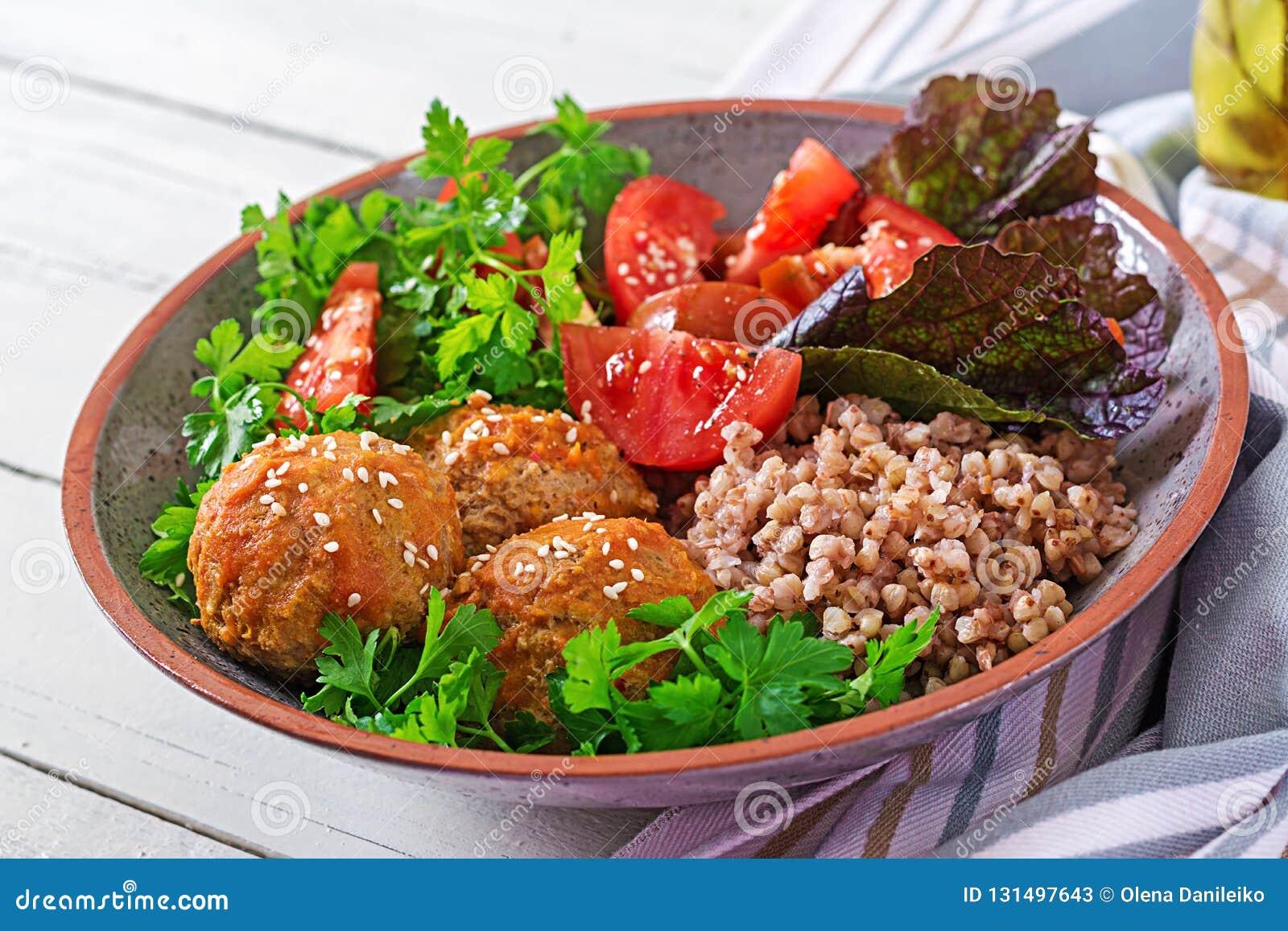Klopsiki, sałatka pomidory i gryczana owsianka na białym drewnianym stole, zdrowa żywność Dieta posiłek Buddha puchar