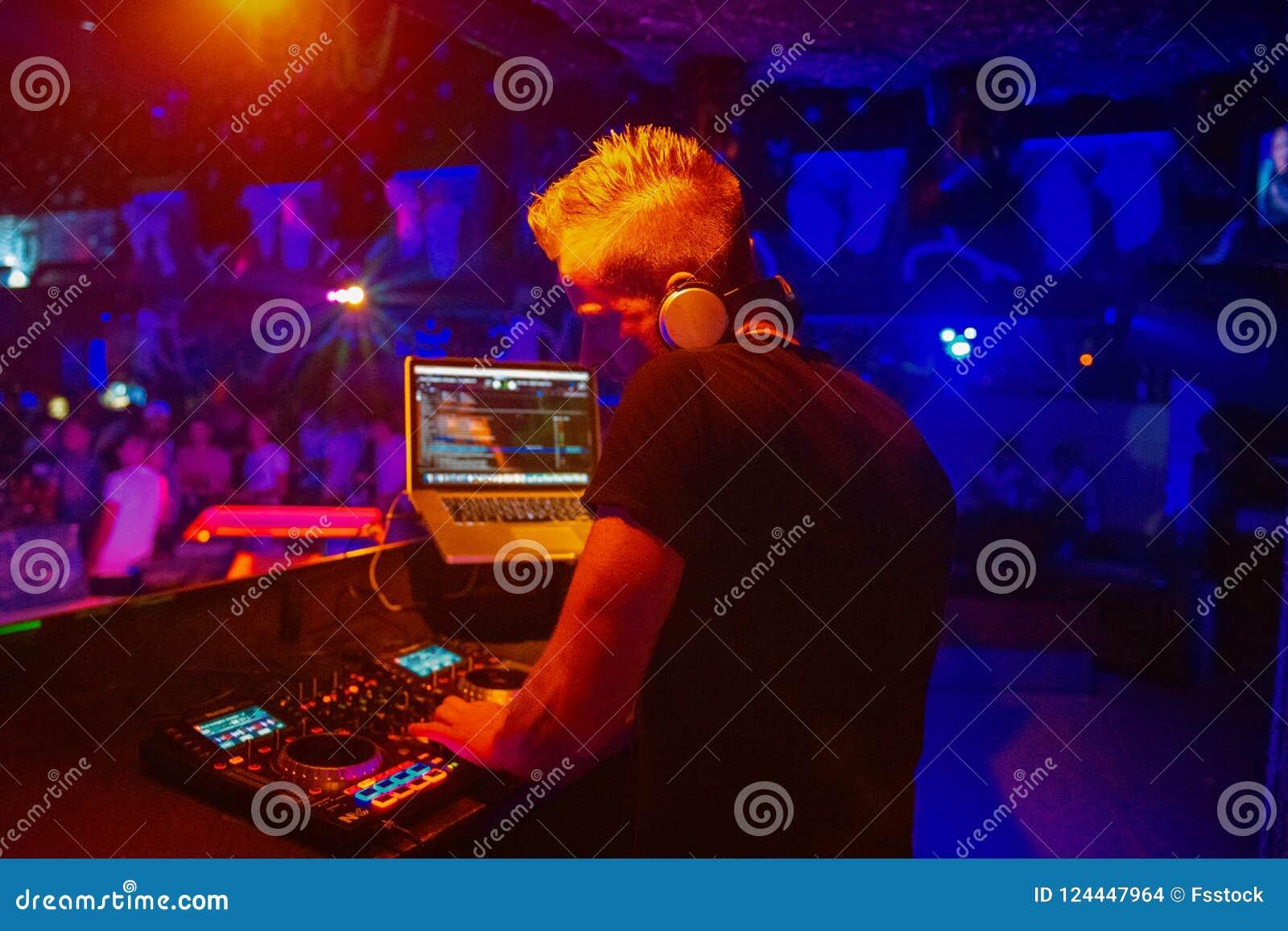 Klubba diskodiscjockey som spelar och blandar musik för folkmassan av lyckligt folk Uteliv konsertljus, signalljus