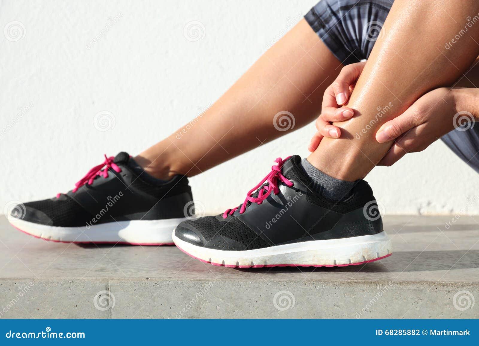 Knöchelschmerz - weiblicher Läufer, der schmerzliche verstauchte gemeinsame Beinnahaufnahme hält