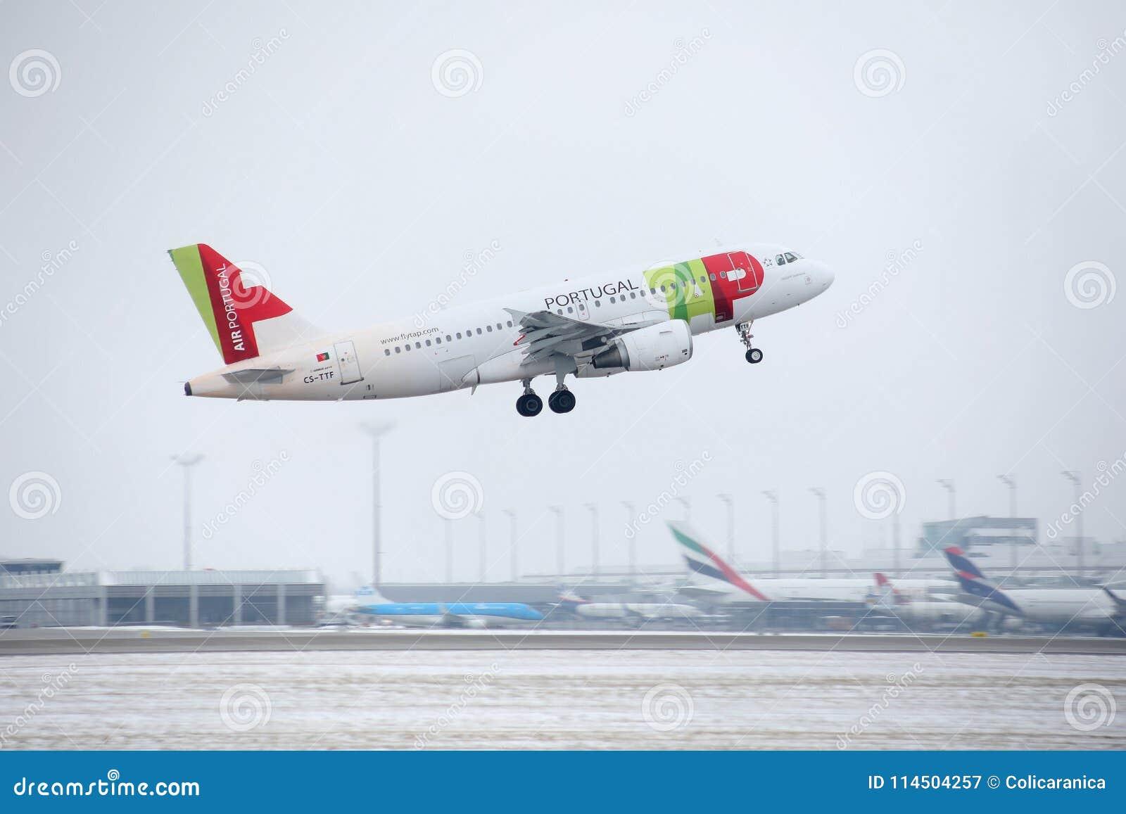 KNACKA LÄTT PÅ den Air Portugal flygbussen A319-100 CS-TTF i den Munich flygplatsen, Tyskland, vintertid med snö