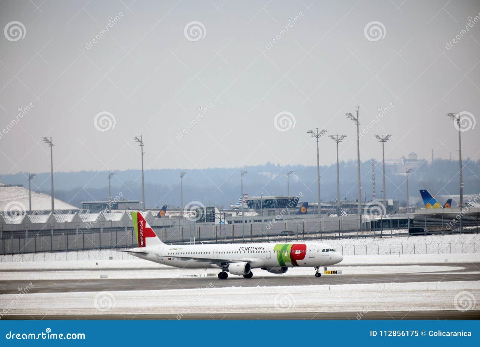 KNACKA LÄTT PÅ den Air Portugal nivån på landningsbana i den Munich flygplatsen, Tyskland, vintertid med snö