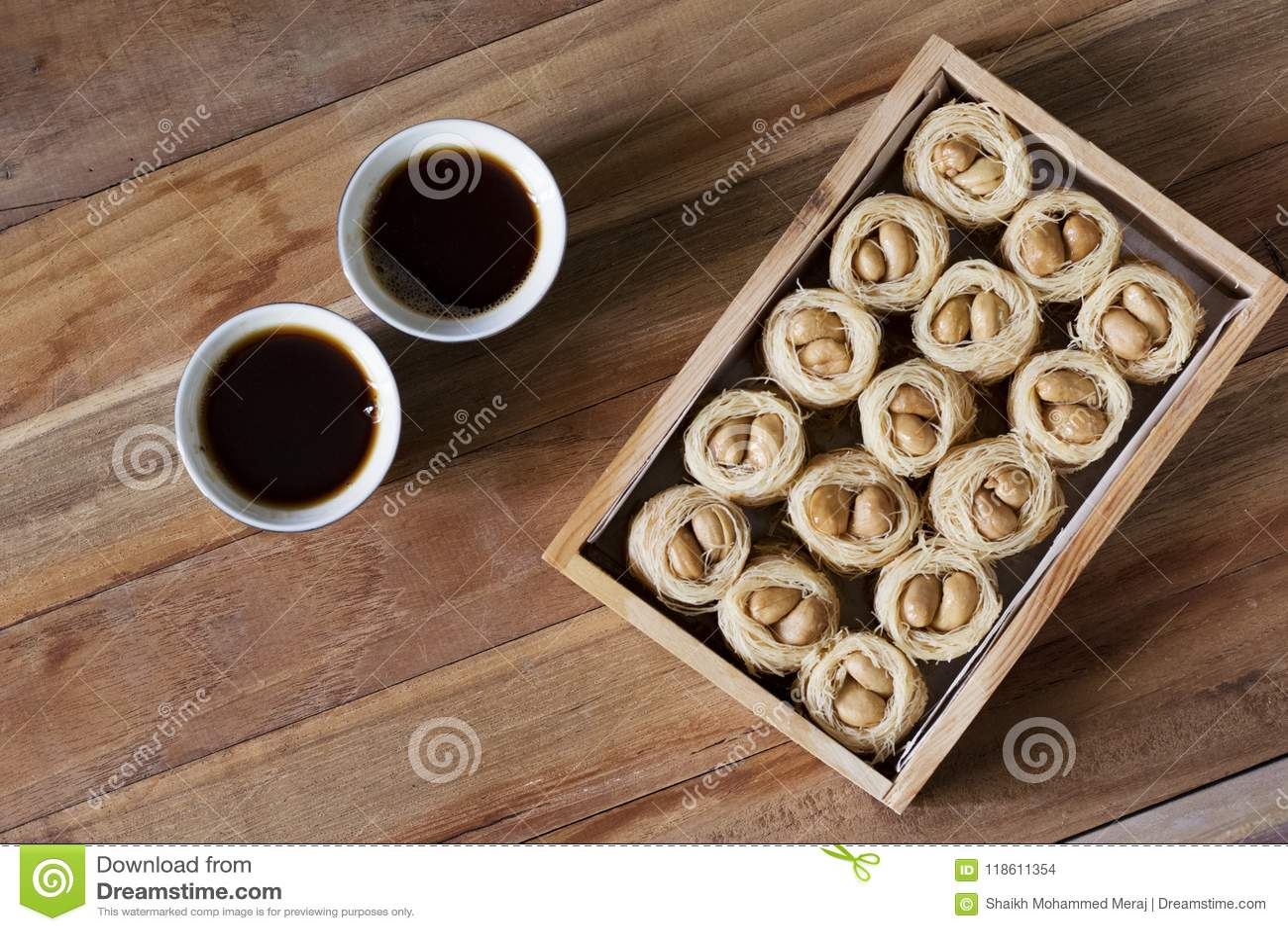 Knafeh de la jerarquía del Bulbul - un bolbol dulce medio-oriental y un café árabe Qahwah del EL del aysh del plato con el fondo