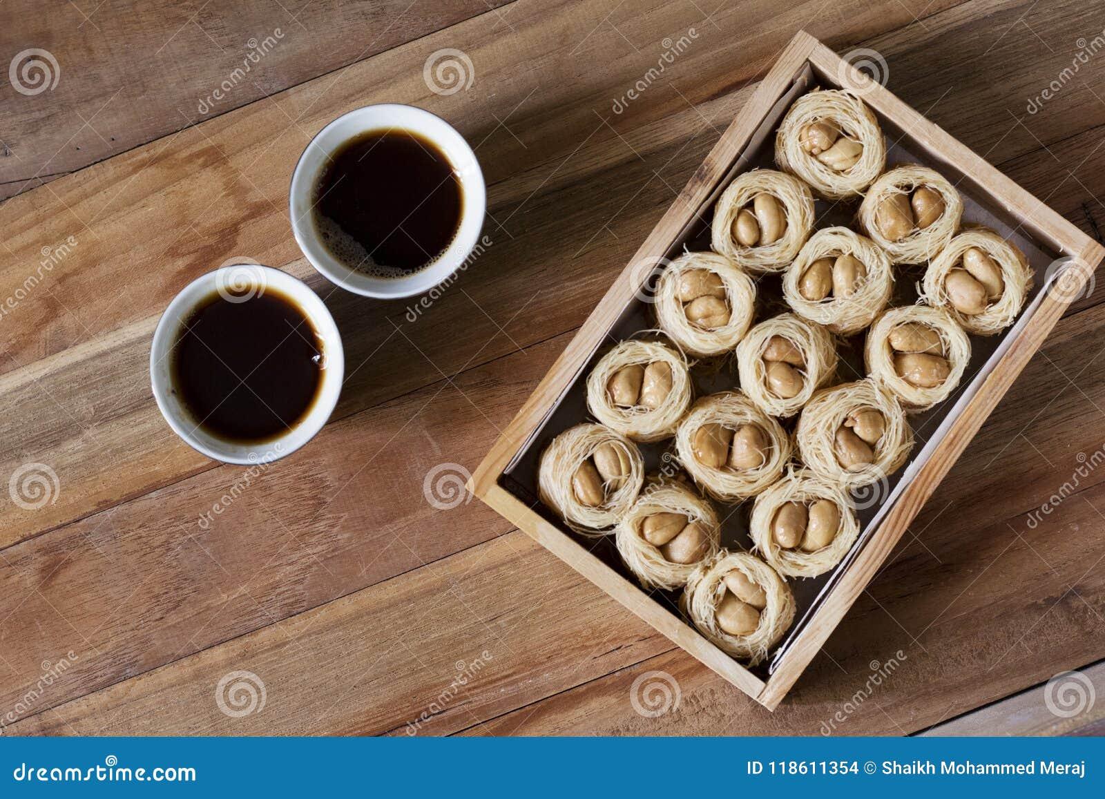 Knafeh do ninho do Bulbul - um bolbol doce do Oriente Médio do EL do aysh do prato e um café árabe Qahwah com fundo de madeira