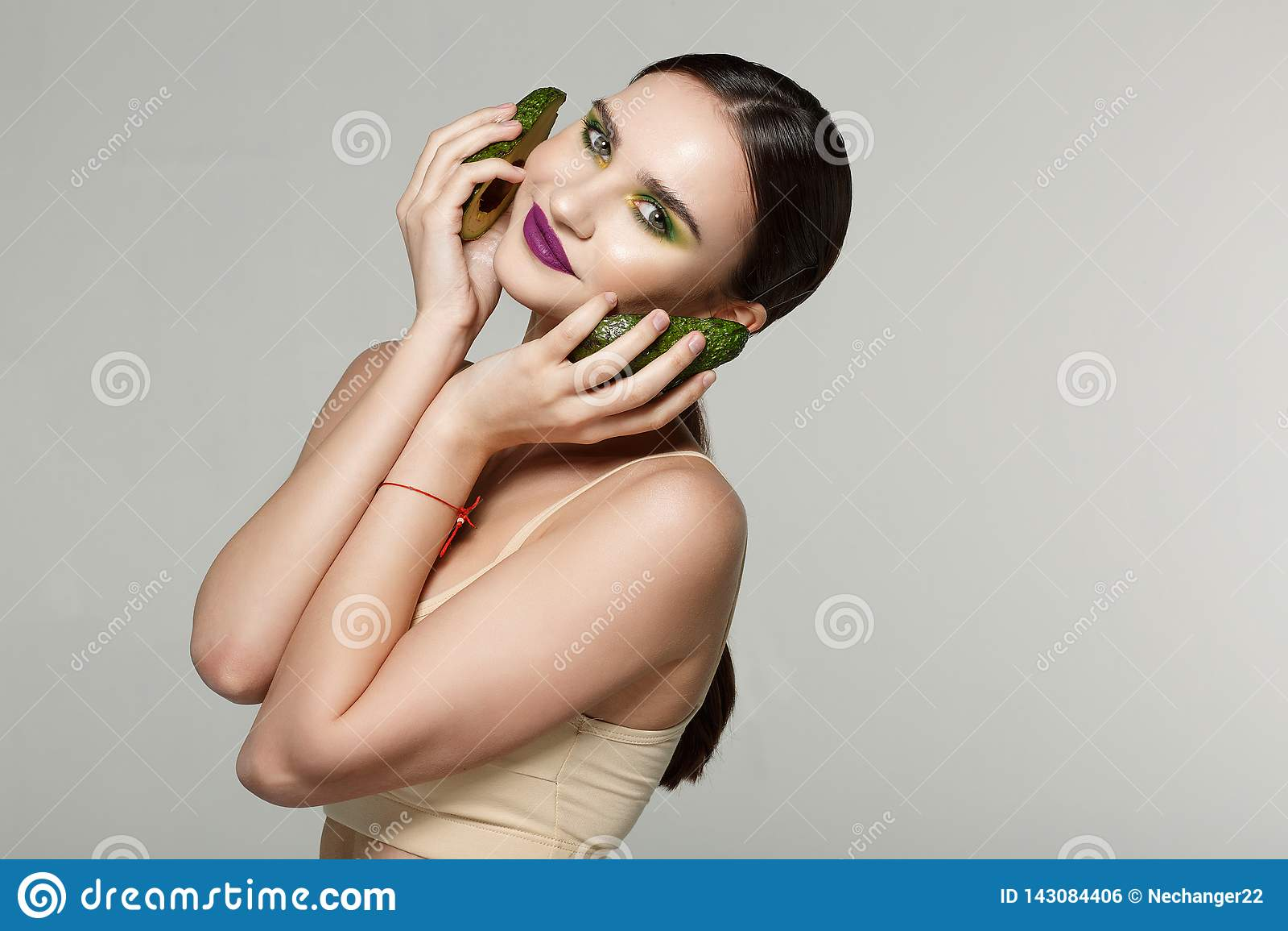 Knap ernstig meisje die met avocado de camera bekijken