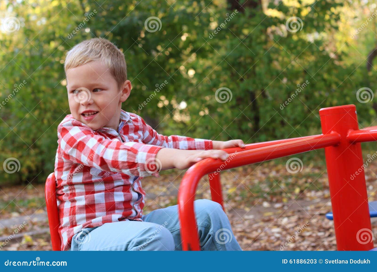 Knap weinig jongen in overhemdsspelen op kleine carrousel