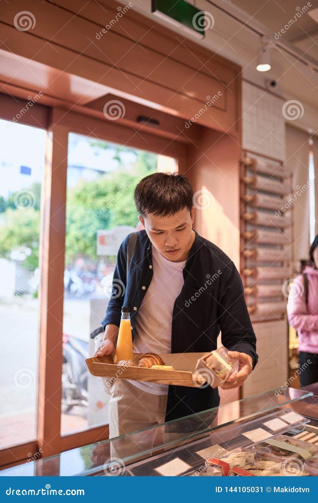 Knappe Aziatische mens het kopen bakkerij voor koffiepauze in de middag Bakkerij en koffiepauze