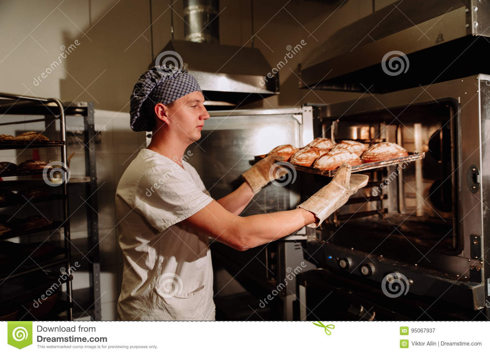 Knappe bakker in het eenvormige hoogtepunt van het holdingsdienblad van vers gebakken brood bij de productie