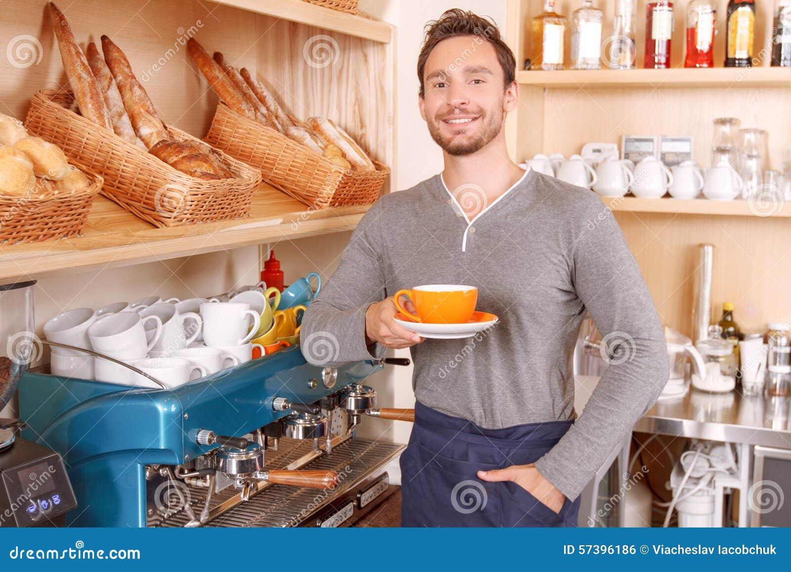 Knappe cafetariaarbeider met kop van koffie