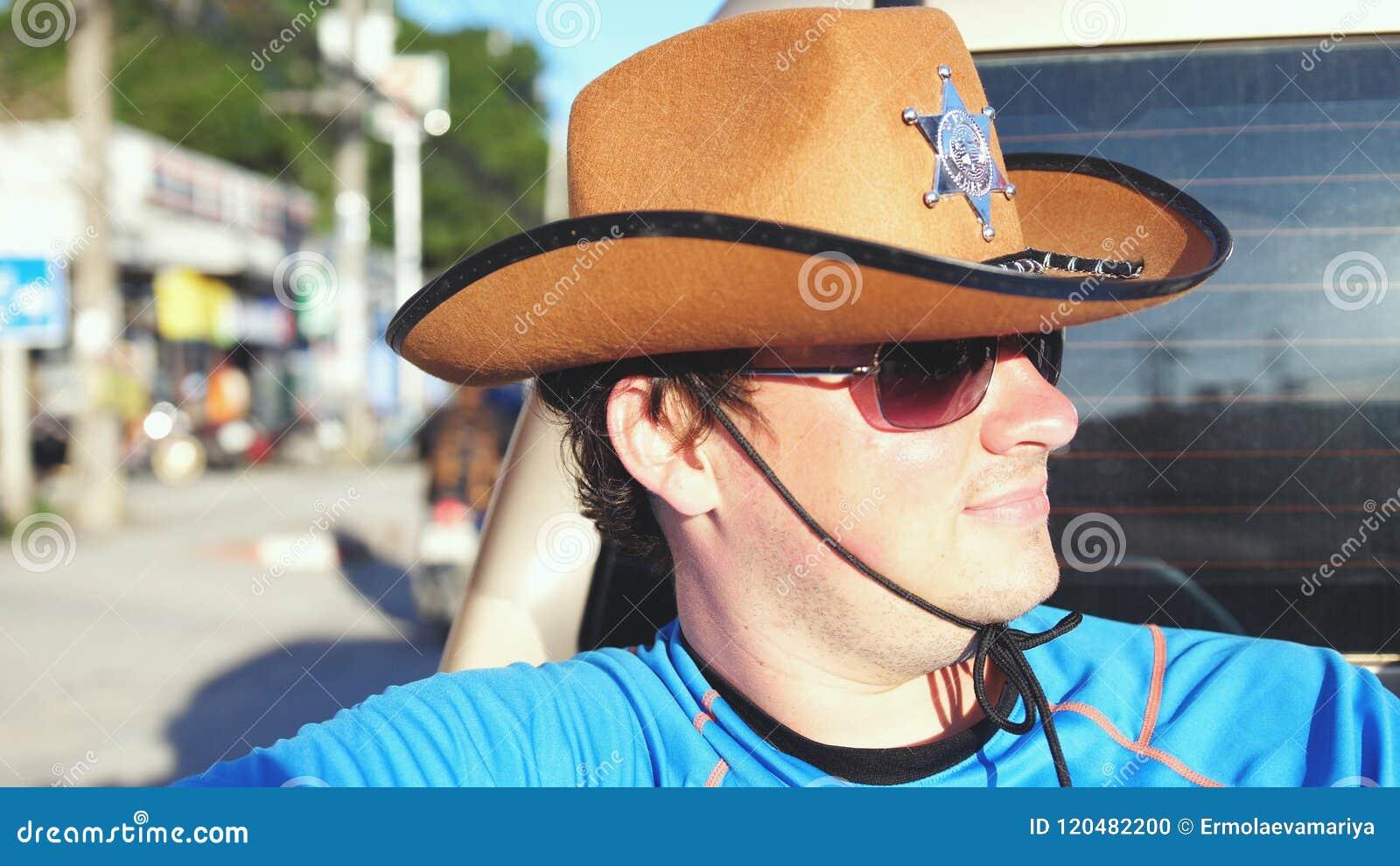 Knappe cowboy in hoed en zonnebril die in een pick-up in zonnige dag reizen