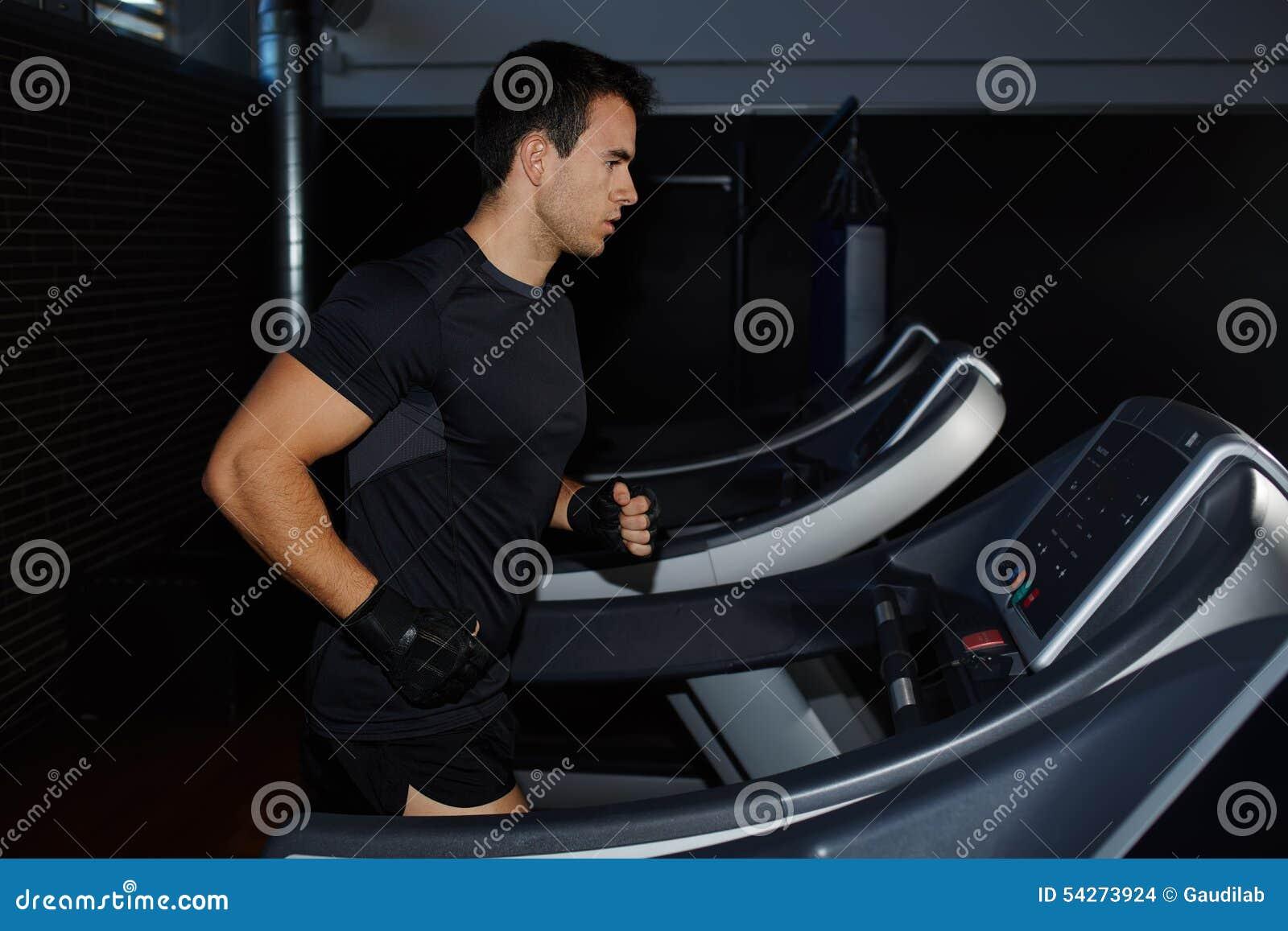 Knappe donkerbruine mens die training in gymnastiek doen die op tredmolen lopen