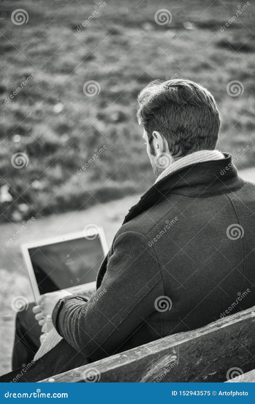 Knappe elegante zakenman die in een park werken