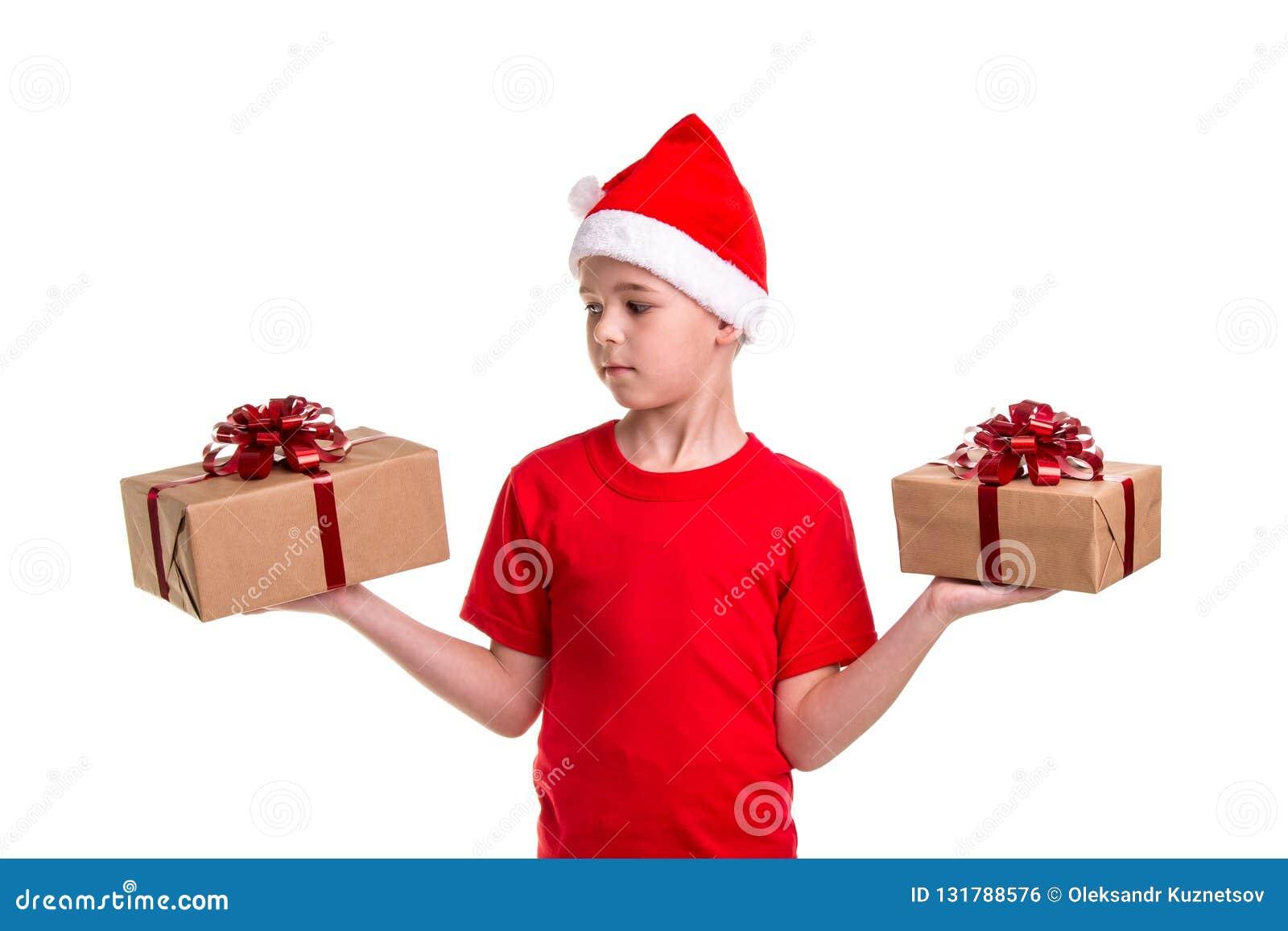 Knappe ernstige jongen, santahoed op zijn hoofd, met twee giftdozen op de handen, die aan de juiste doos kijken Concept