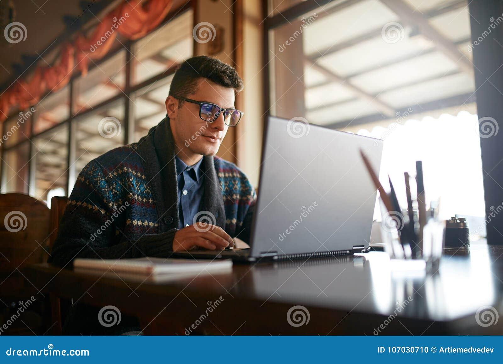 Knappe freelancerzakenman die aan laptop in koffie werken Bloggermens die zijn profiel in sociale netwerken bijwerken met