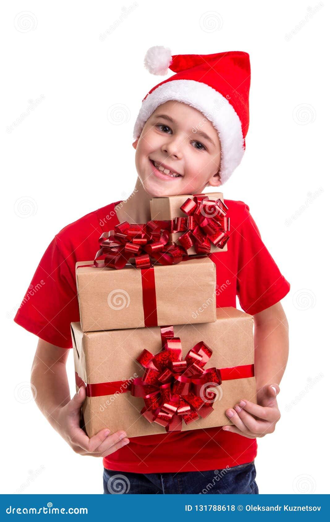 Knappe gelukkige jongen, santahoed op zijn hoofd, met bos van de giftdozen in de handen Concept: Kerstmis of Gelukkige Nieuw