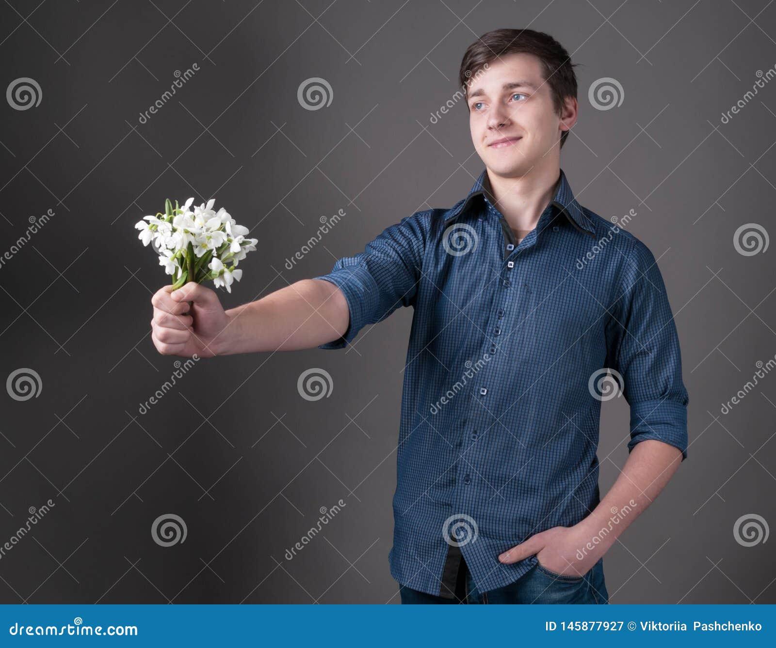Knappe glimlachende jonge mens in blauwe overhemdsholding in uitgestrekt handboeket met witte sneeuwklokjes