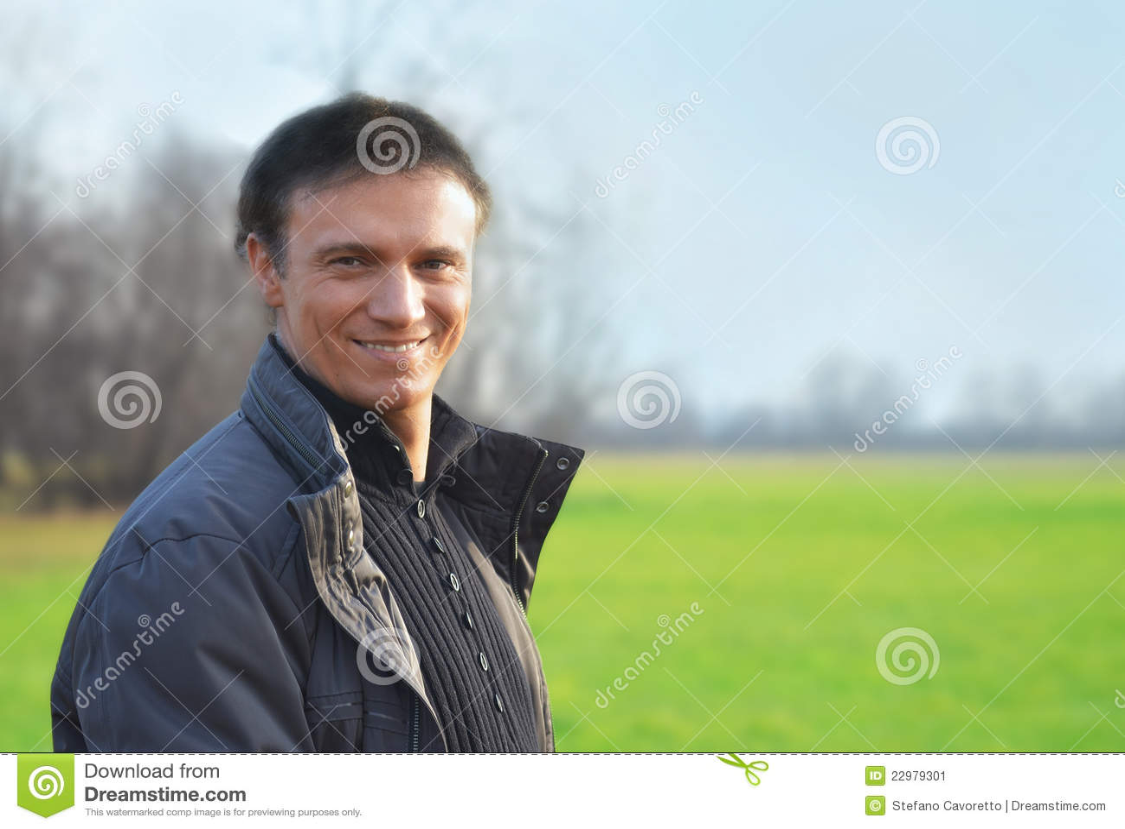 Knappe glimlachende mens in openlucht