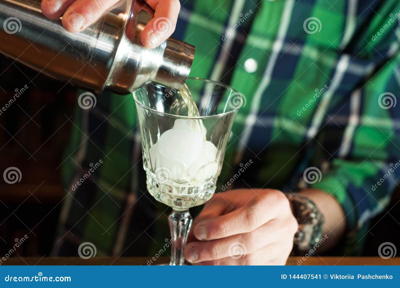 Knappe jonge barman in groen overhemd die en zich dichtbij houten teller in bar bevinden werken