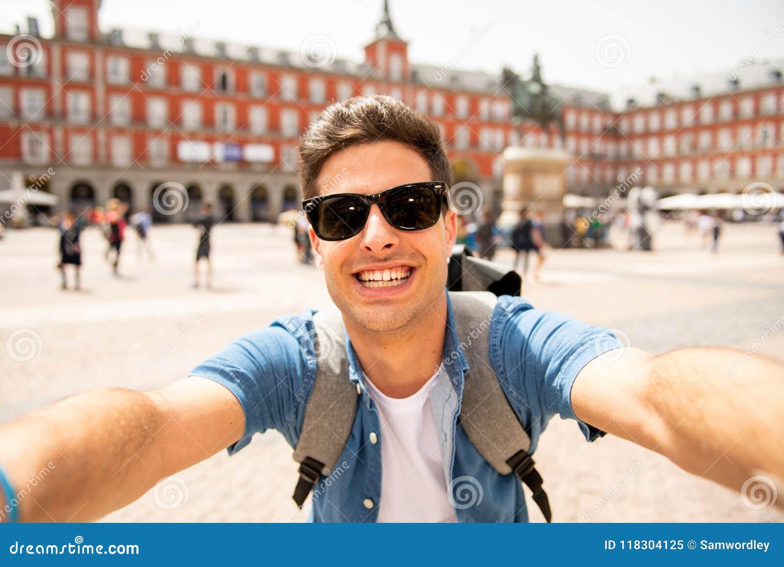 Knappe jonge Kaukasische gelukkig en opgewekte toeristenmens nemend een selfie in Pleinburgemeester, Madrid Spanje