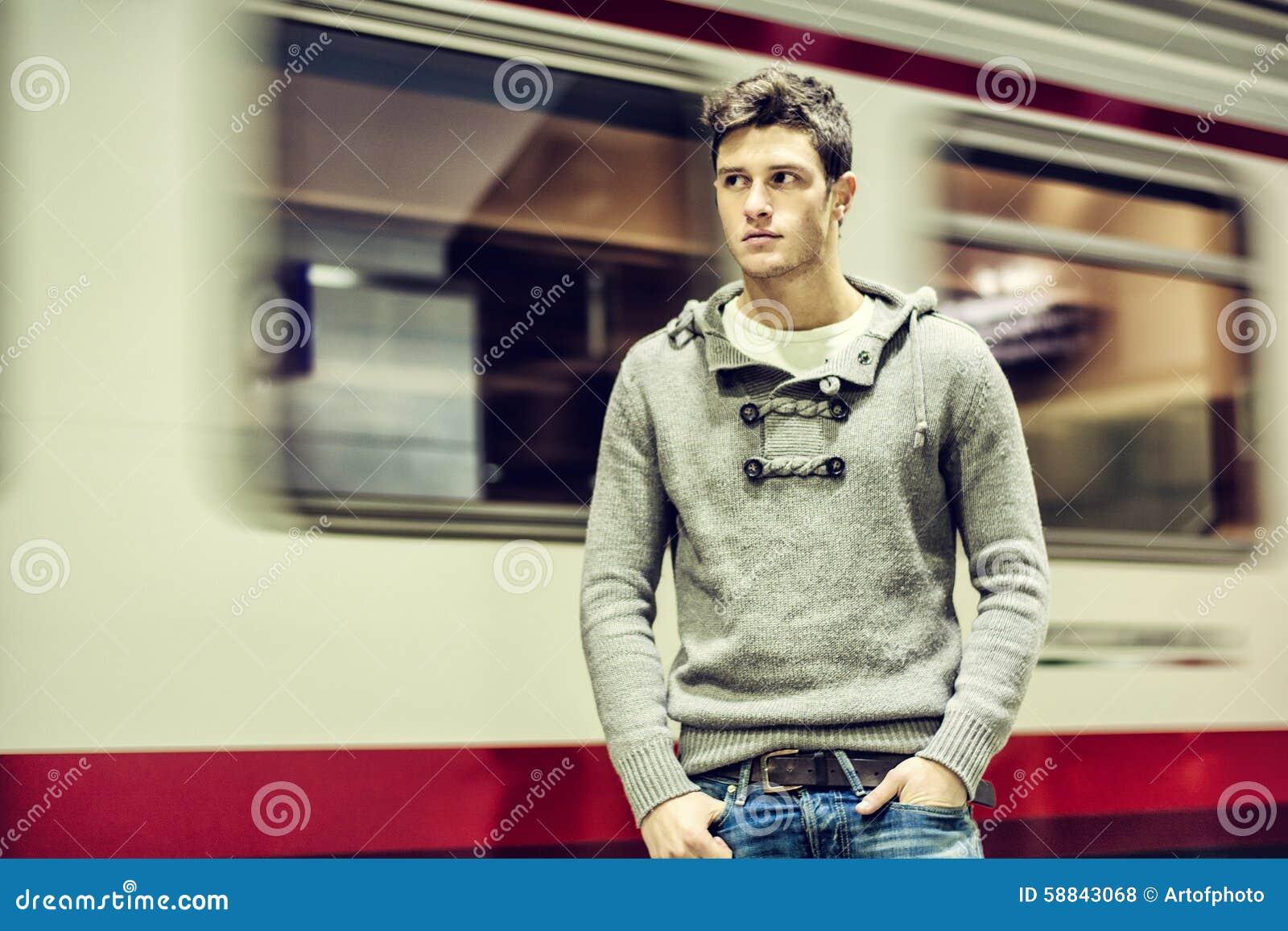 Knappe jonge mens binnen station het kijken