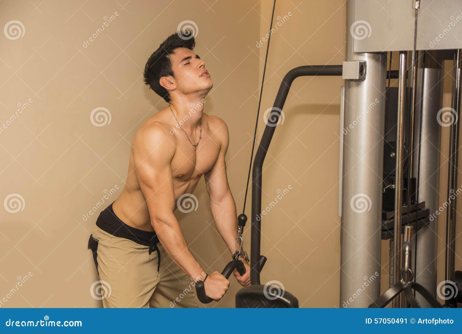 Knappe jonge mens die op gymnastiekmateriaal uitwerken