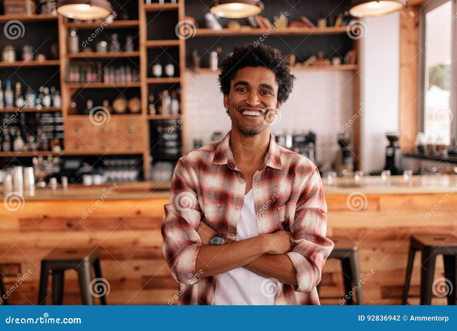 Knappe jonge mens met zijn die wapens in een koffie worden gekruist
