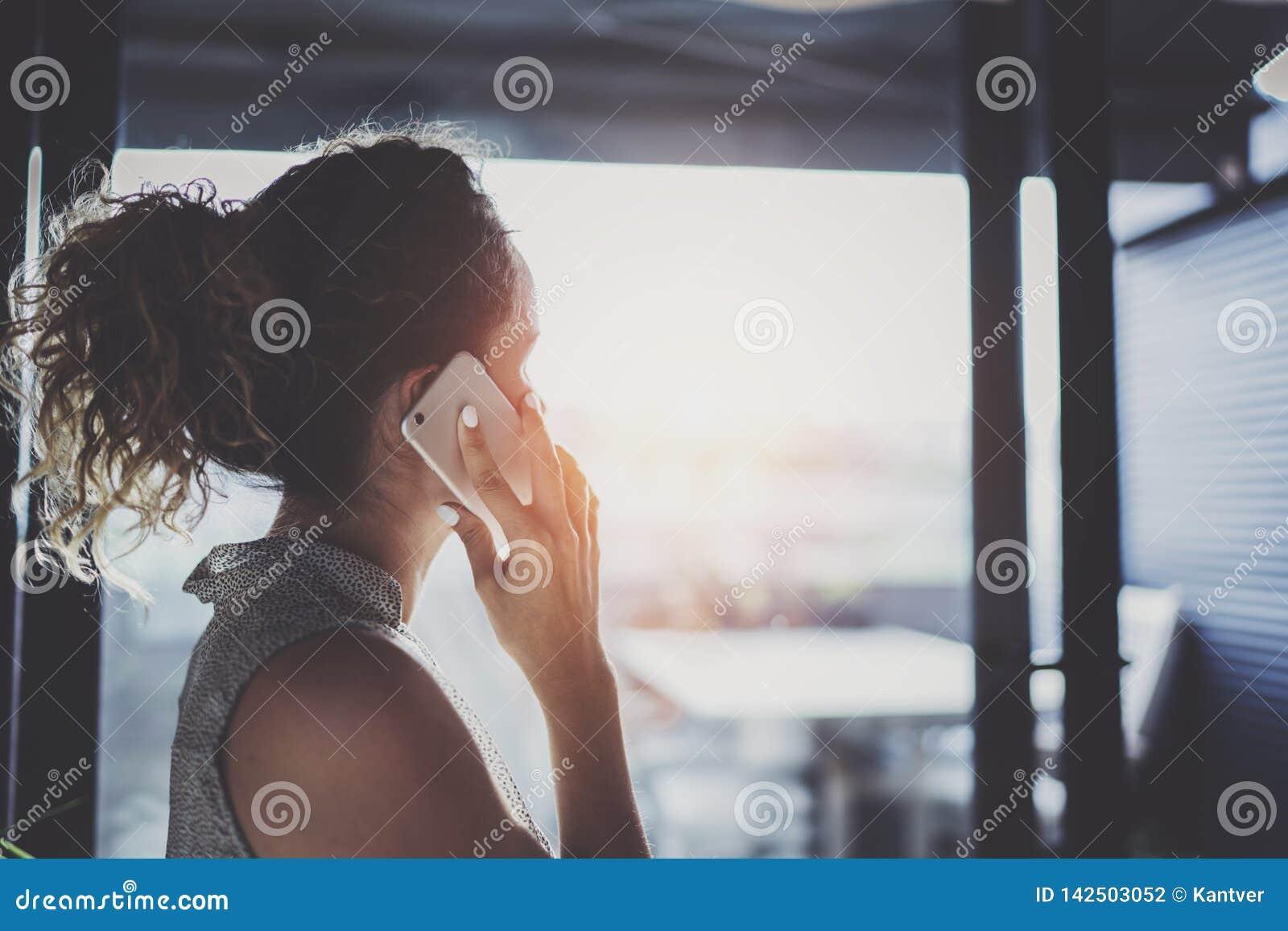 Knappe jonge vrouw die met vrienden via moderne smartphone spreken terwijl het doorbrengen van haar tijd bij moderne stedelijke k