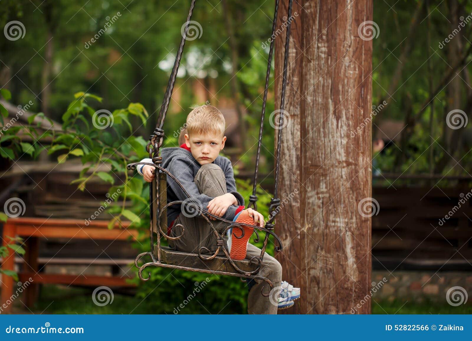 Knappe jongen met een droevig die gezicht op de bank in de zomer D wordt gesitueerd