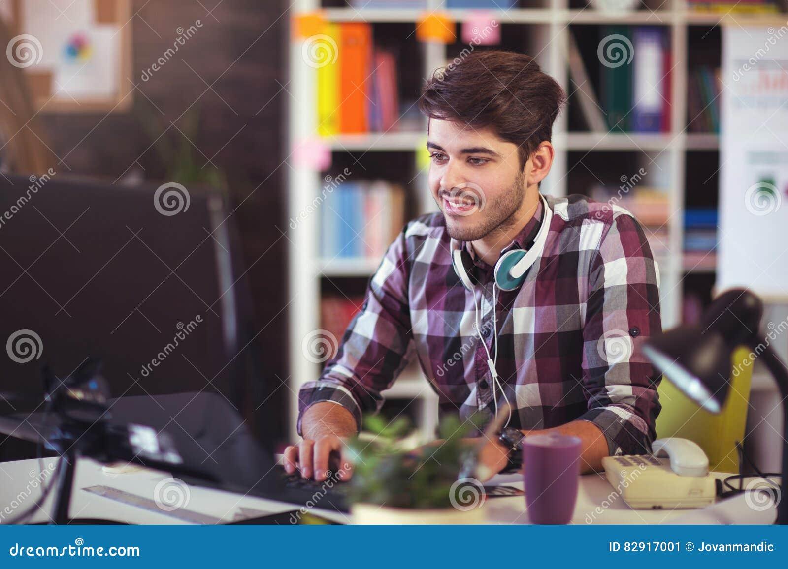Knappe Kaukasische mens bij het werkbureau die vlakke het schermcomputer onder ogen zien