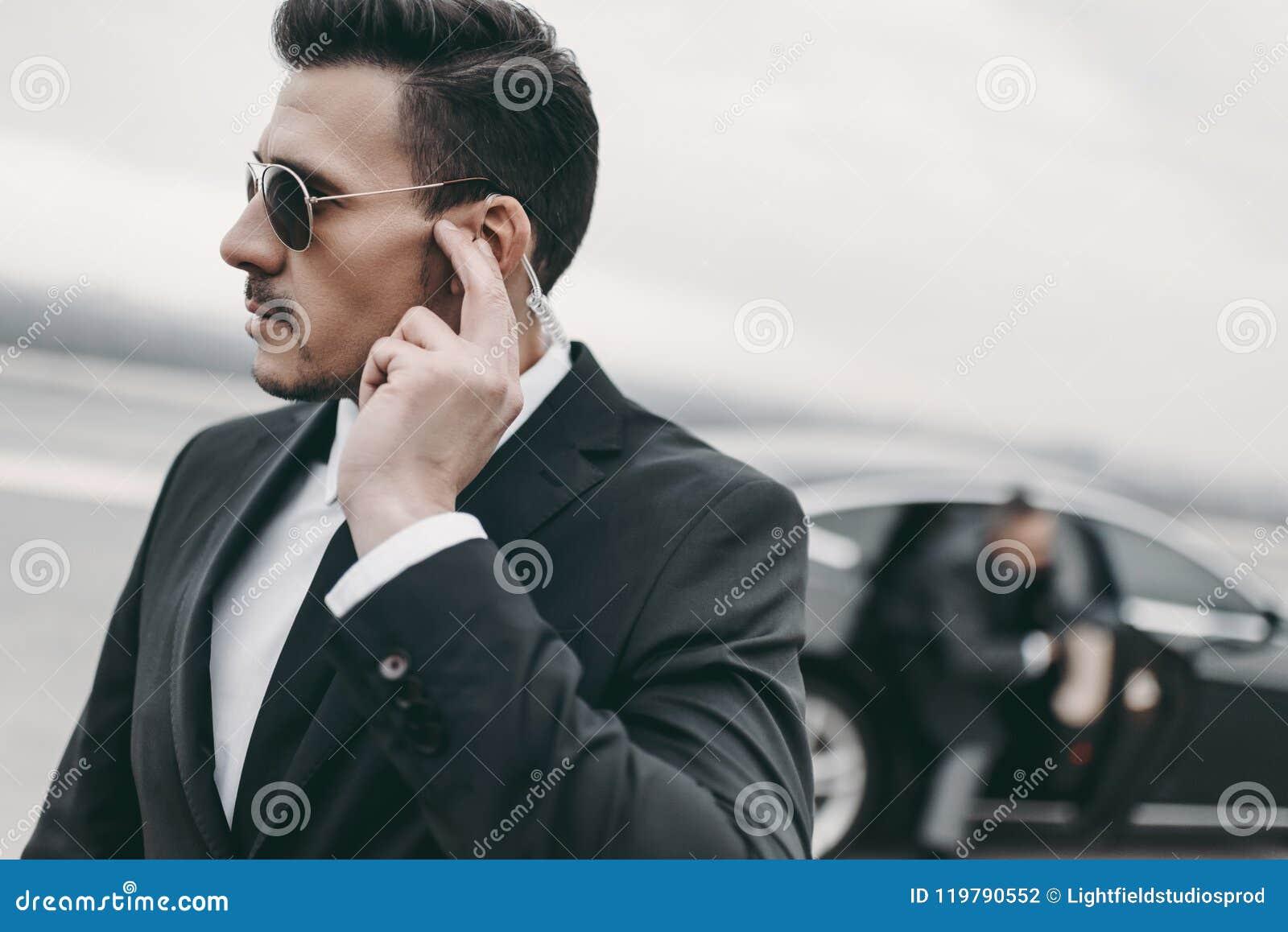 Knappe lijfwacht van zakenman het luisteren bericht