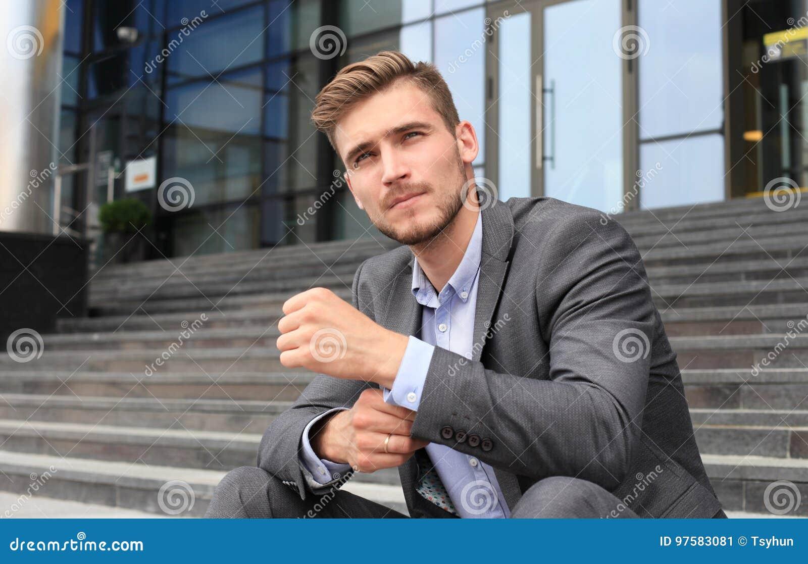 Knappe mannelijke directeurzitting op treden buiten een gebouw
