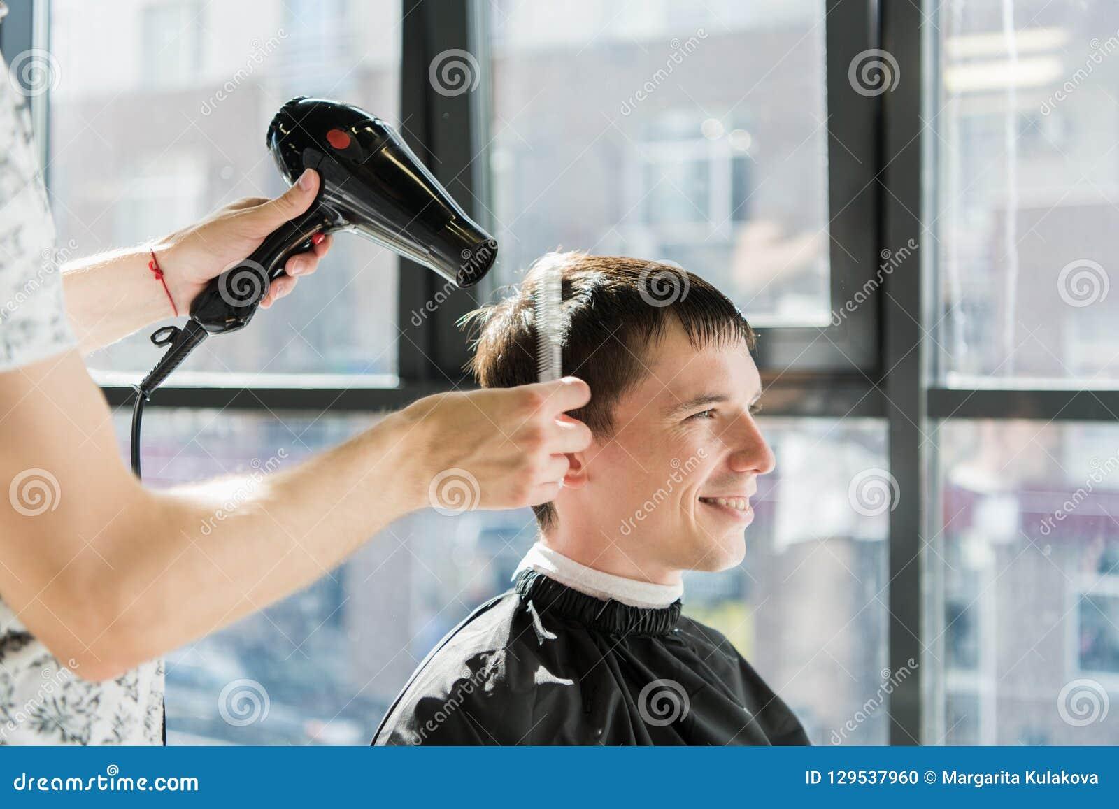 Knappe mens bij de kapper die een nieuw kapsel krijgen