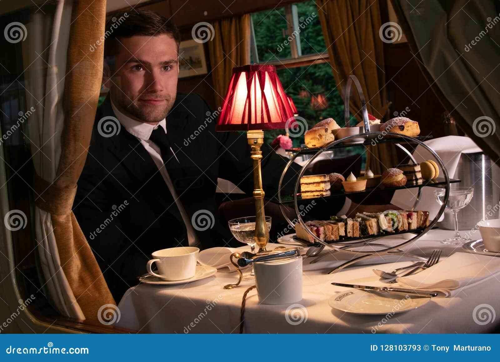 Knappe mens die in kostuum middag van thee in uitstekend treinvervoer genieten