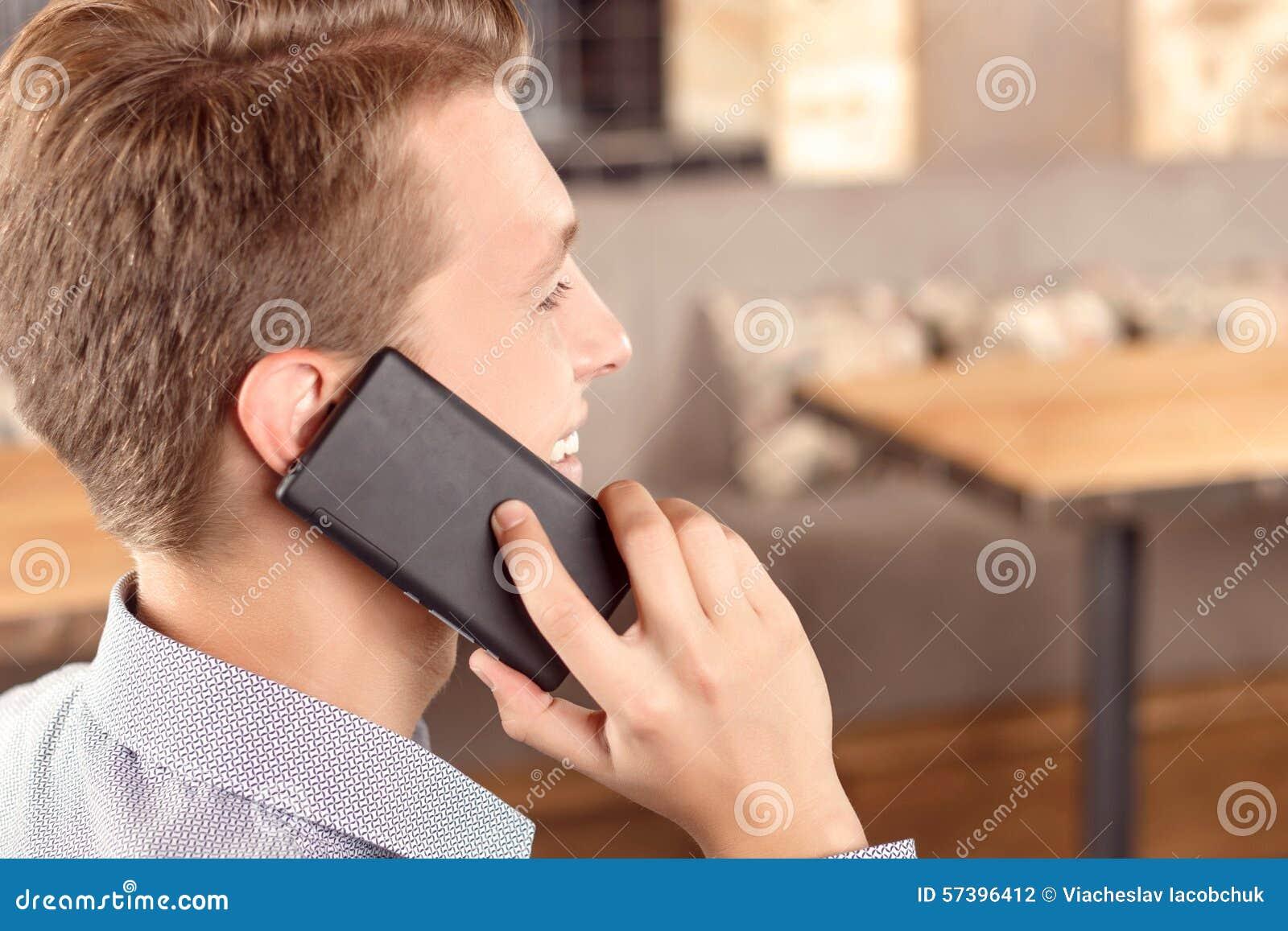 Knappe mens die per mobiele telefoon spreken