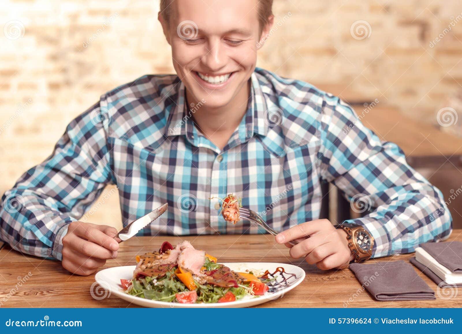 Knappe mens die salade in koffie eten