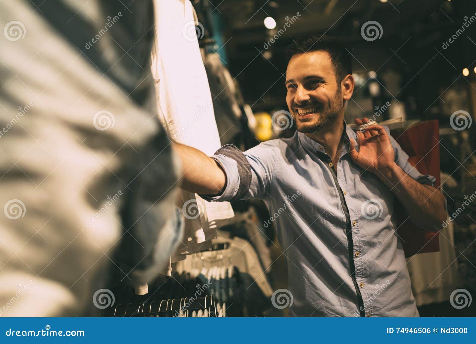 Knappe mens die voor kleren winkelen