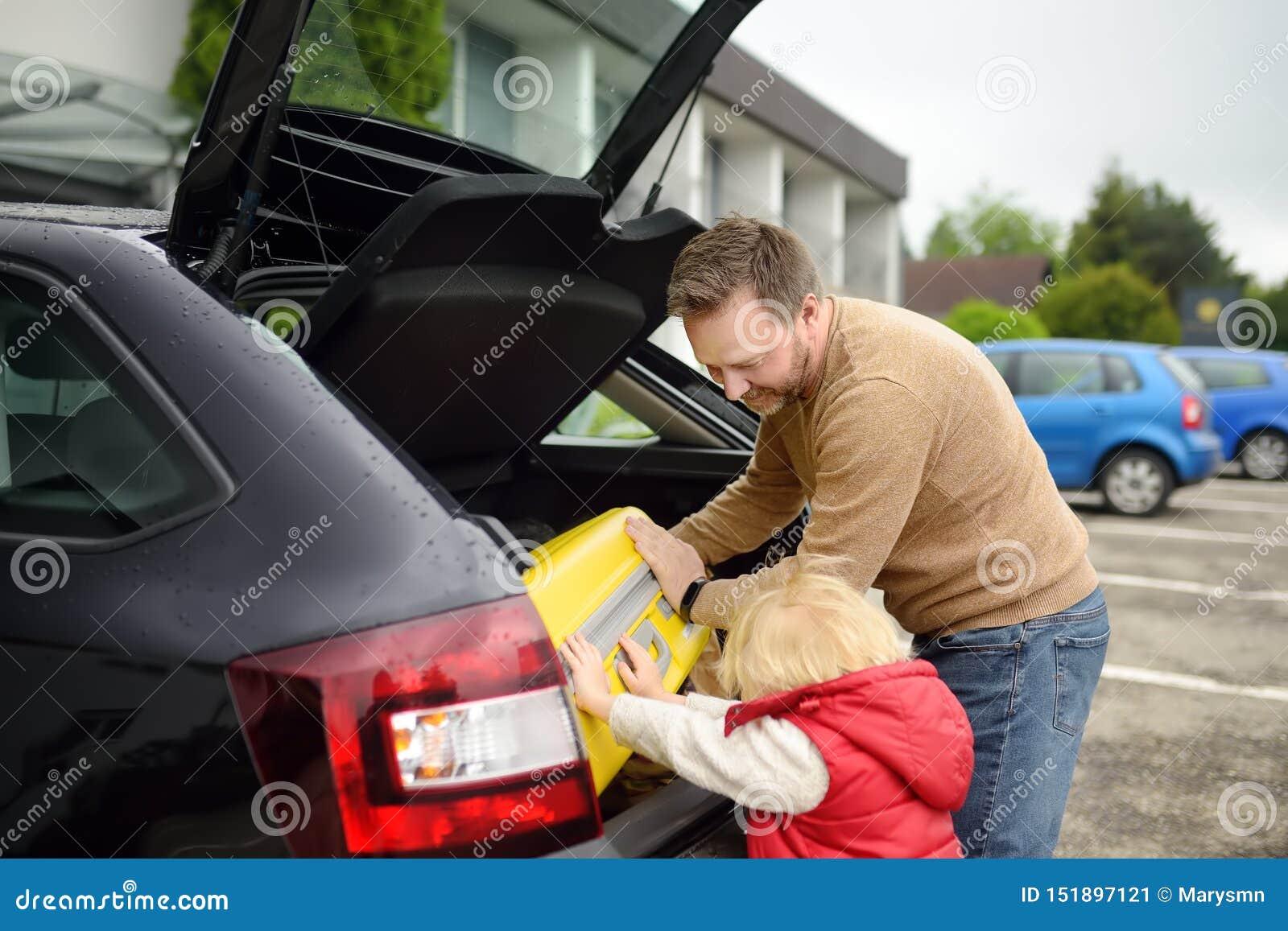 Knappe mens en zijn kleine zoon die naar vakanties gaan, die hun koffer in autoboomstam laden Automobiele reis in het platteland