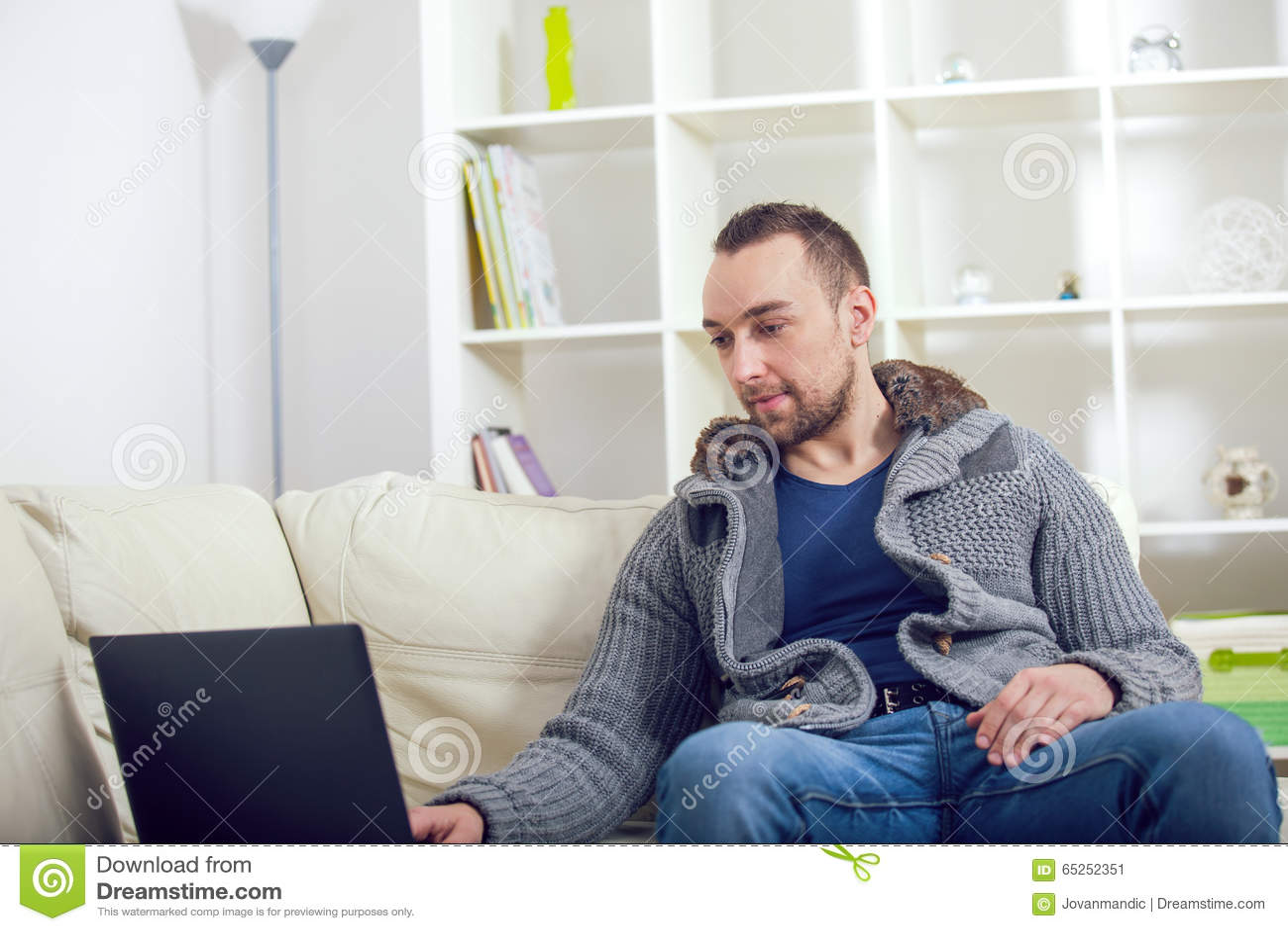 Knappe mensenzitting op bank met laptop
