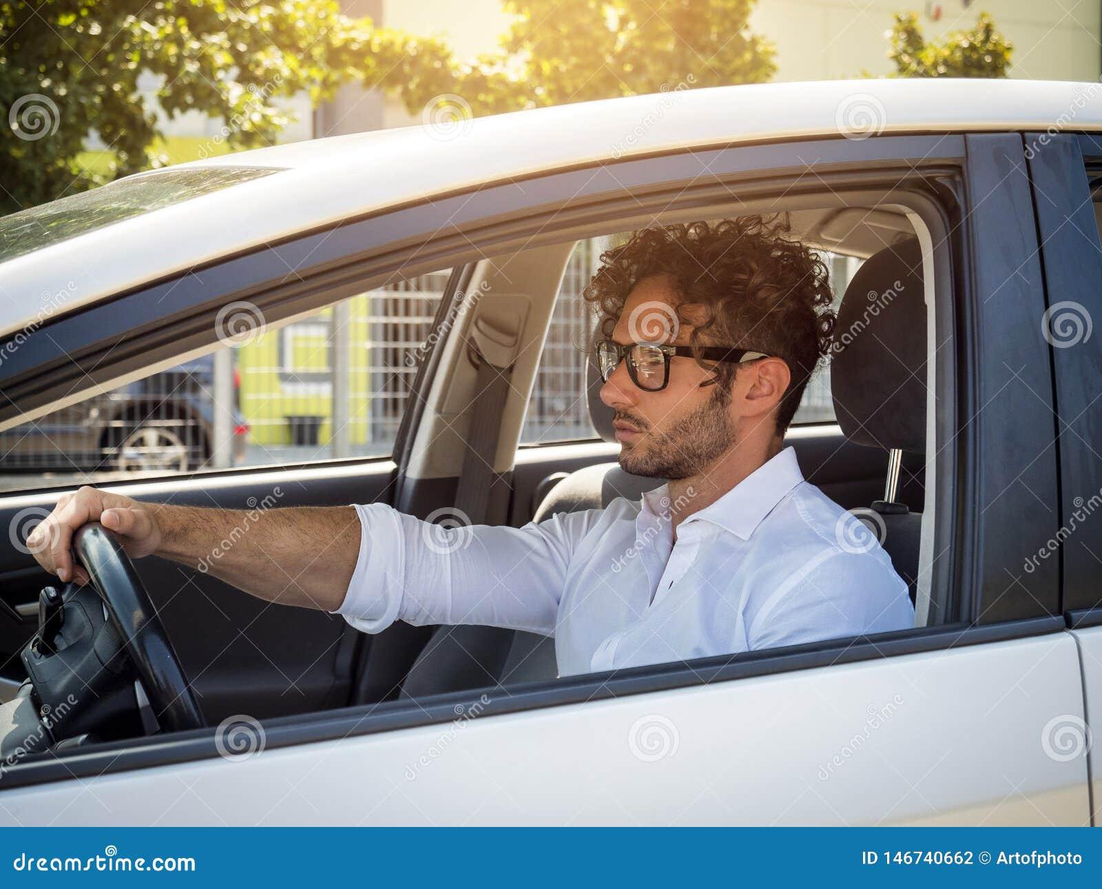 Knappe mensenzitting in zijn auto, die weg eruit zien