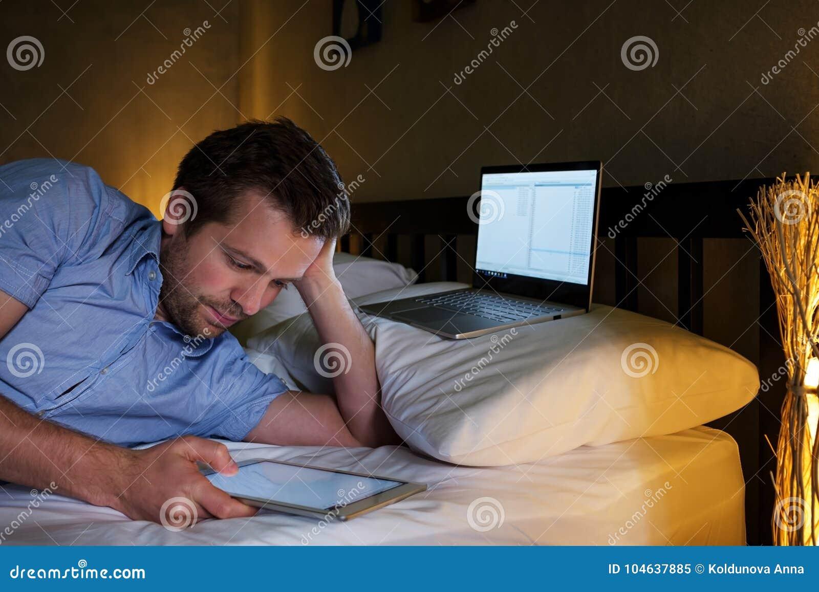 Download Knappe Ondernemersmens Die Internet In Bed Doorbladeren Bij Nacht Stock Afbeelding - Afbeelding bestaande uit comfortabel, toevallig: 104637885
