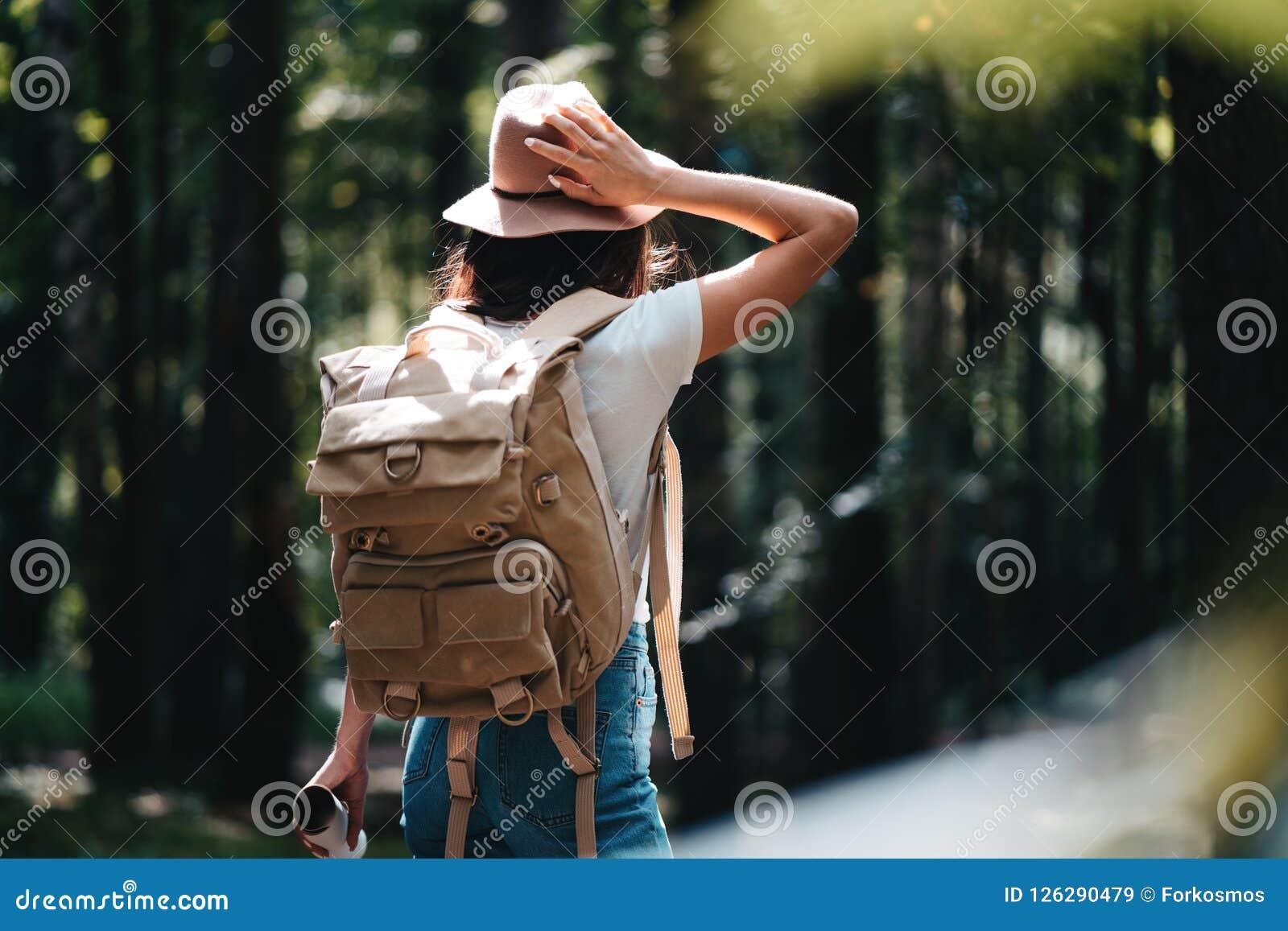 Knappe reizigersvrouw met rugzak en hoed die zich in het bos Jonge hipstermeisje lopen onder bomen op zonsondergang bevinden
