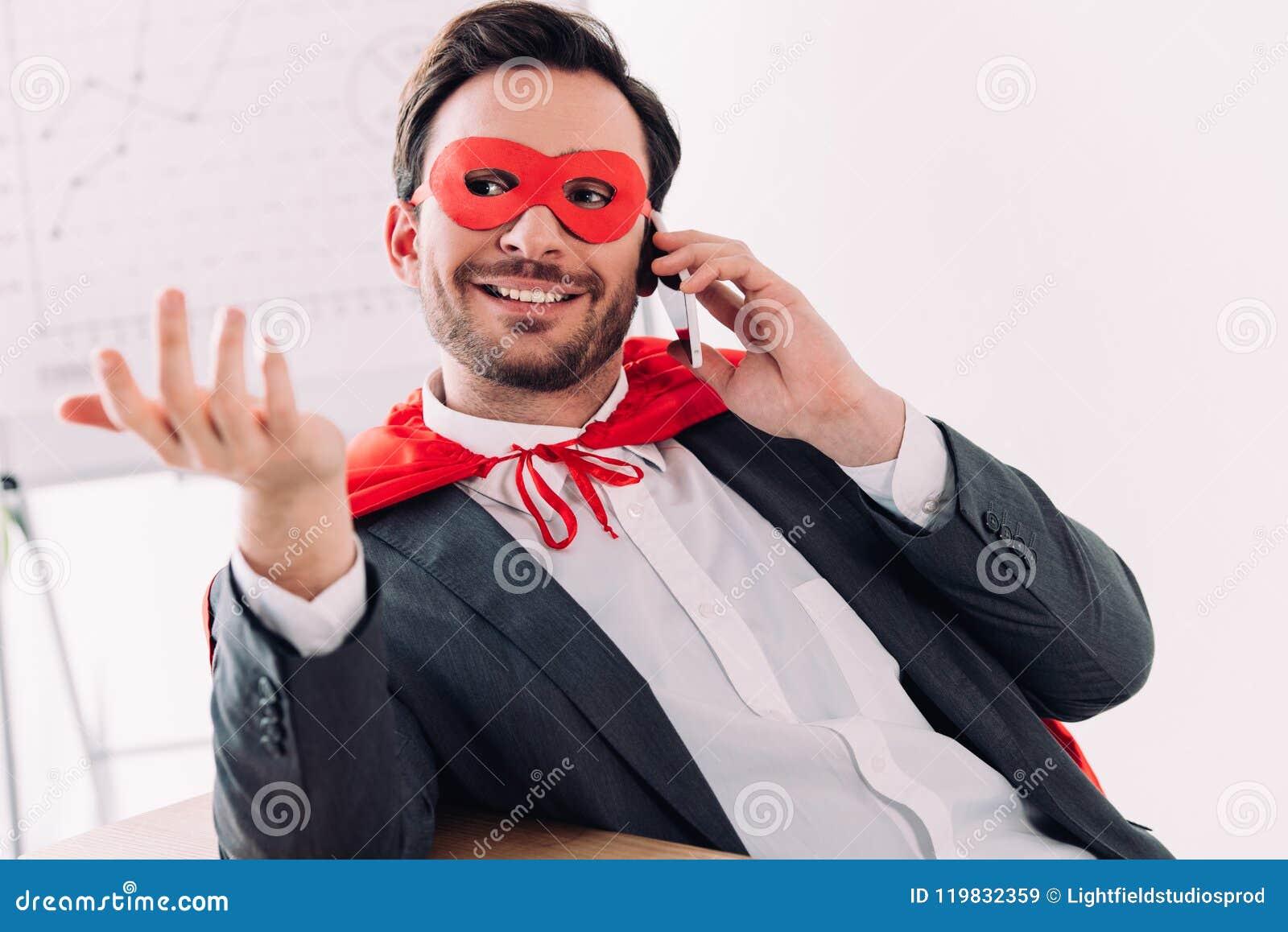 Knappe super zakenman in masker en kaap die door smartphone spreken