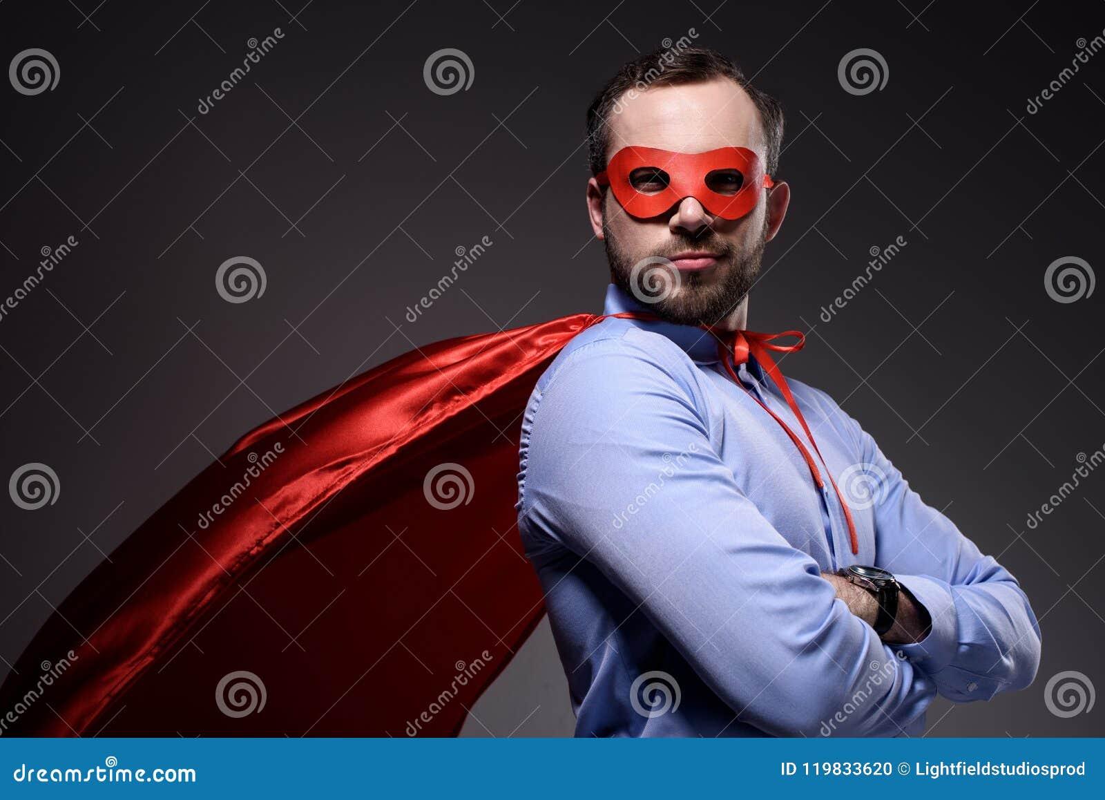 Knappe super zakenman in masker en kaap met gekruiste wapens die camera bekijken