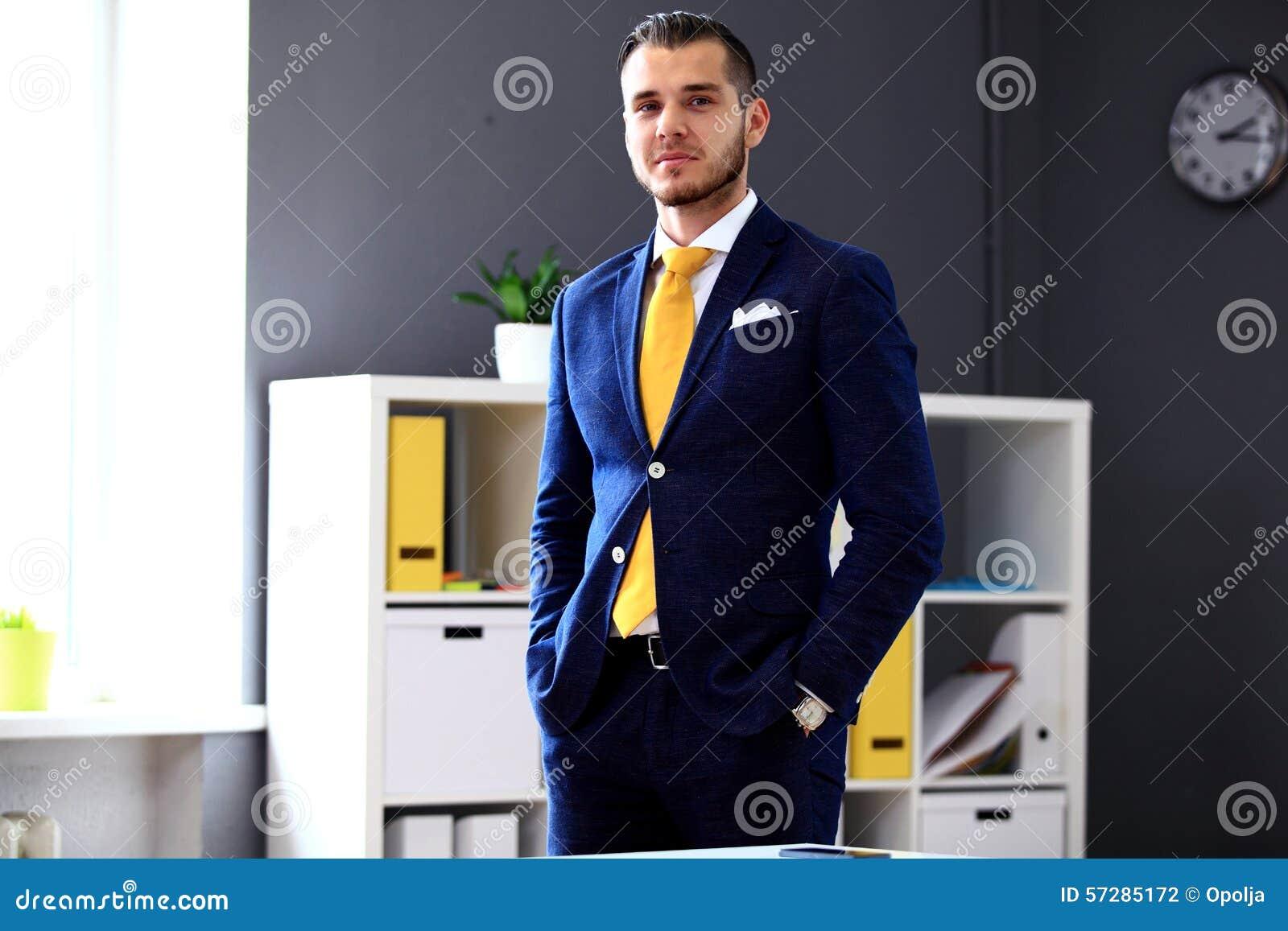Knappe zakenman die in kostuum camera bekijken