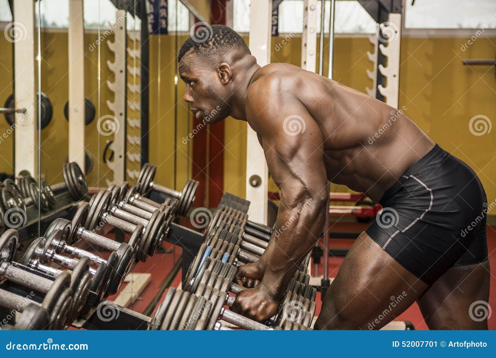 Knappe zwarte mannelijke bodybuilder die na training in gymnastiek rust